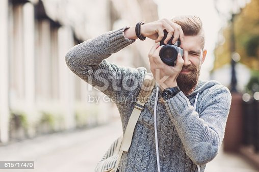Young man photographer holding a camera and taking pictures