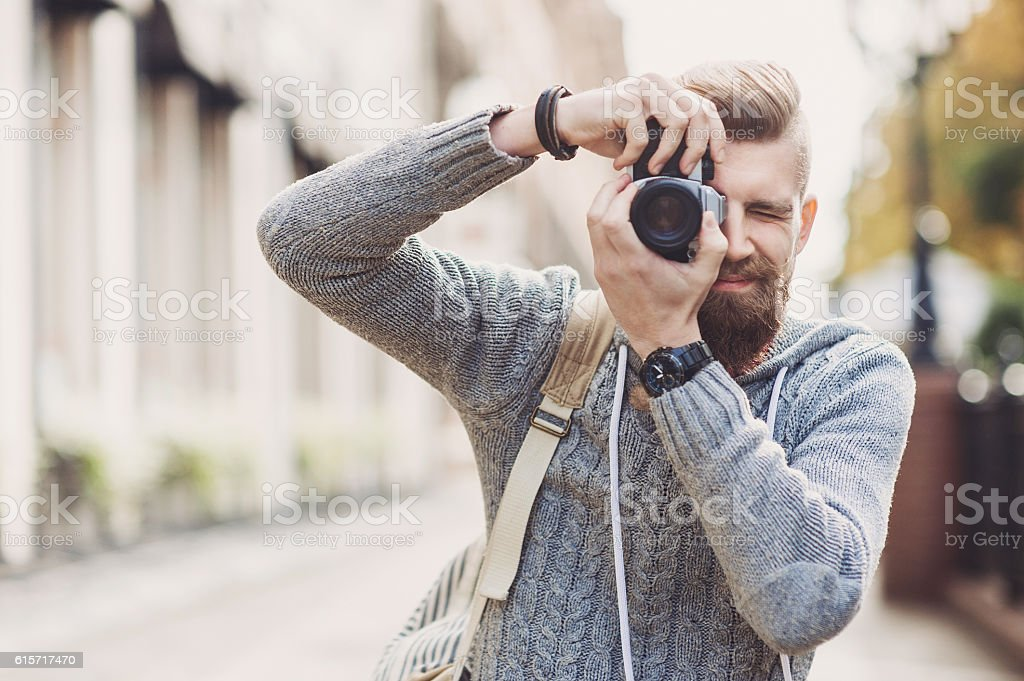 Young man photographer looking at camera stock photo