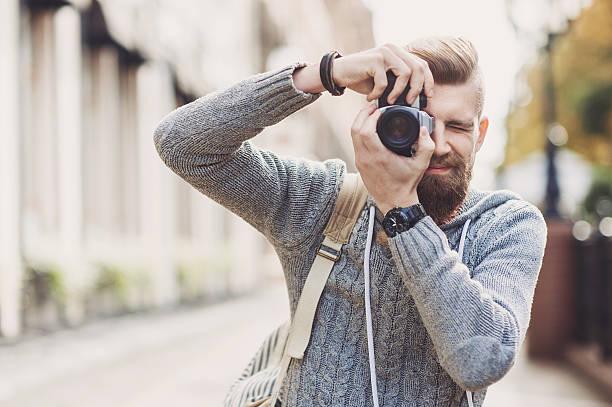 young man photographer looking at camera - spiegelreflexcamera stockfoto's en -beelden