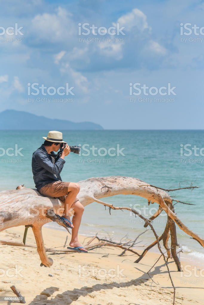 young man photographer sitting on dead tree and taking photos royalty-free stock photo