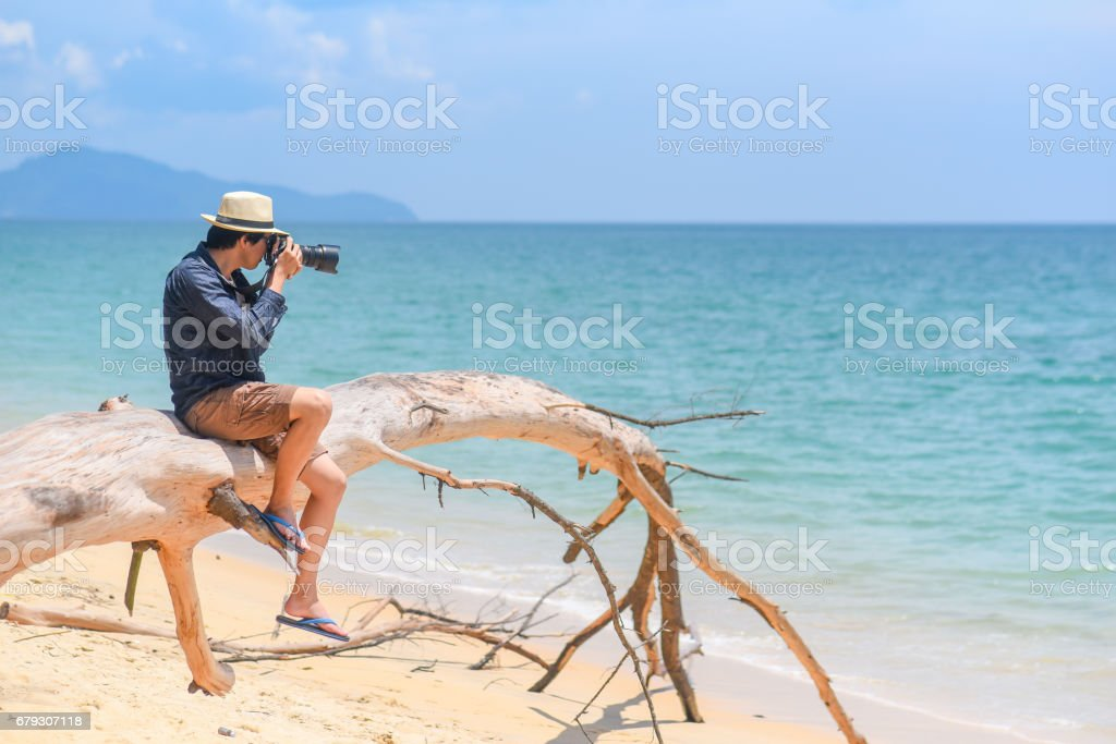 young man photographer take photos on the beach stock photo