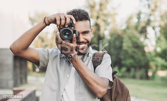 Cheerful men photographer with digital camera