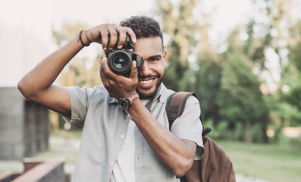 Young man photographer taking pictures in a city stock photo