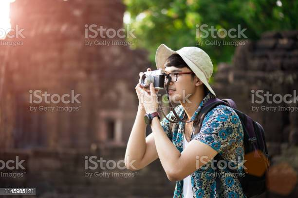 Young man photographer traveler with backpack taking photo with his picture id1145985121?b=1&k=6&m=1145985121&s=612x612&h=q2uhpgoi77d2e loopbmpq2btw7uir 6pjl1qbub4c8=