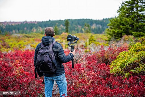 istock Young man photographer with camera and tripod stabilizing gimbal hiking on autumn Bear Rocks trail in Dolly Sods, West Virginia filming video of red huckleberry bushes 1322531707