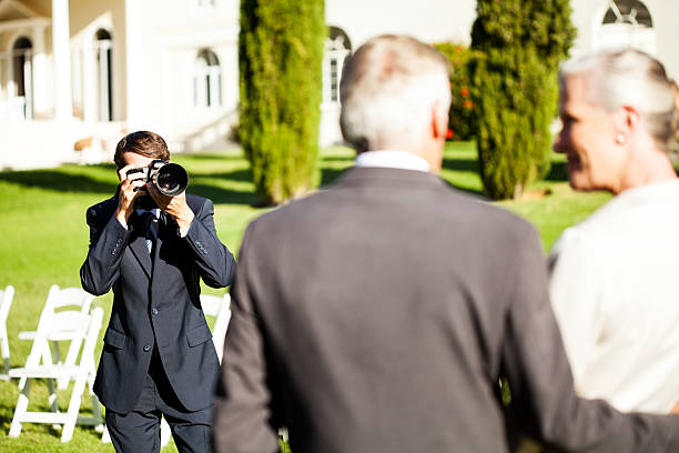Young man photographing couple at outdoor wedding picture id175569129?b=1&k=6&m=175569129&s=612x612&w=0&h=f7pm9sn6eptirev4ks nzav0619eoyog0e7pn3xrghc=