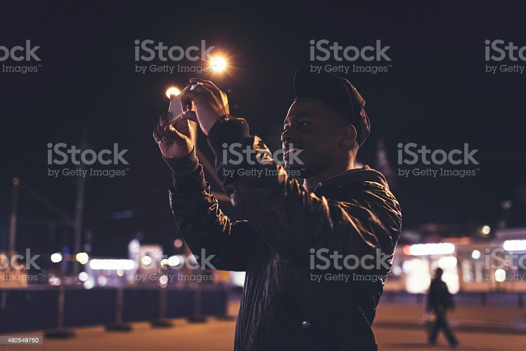 Young man photographing with his mobile in city at night. stock photo