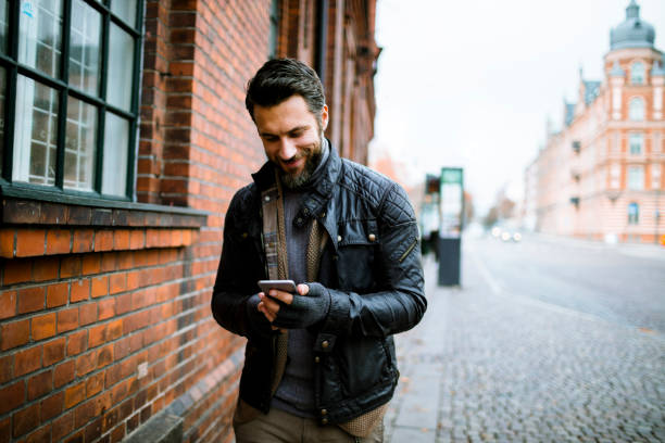 Young Man Close up of a young man using his phone in the city leather jacket stock pictures, royalty-free photos & images