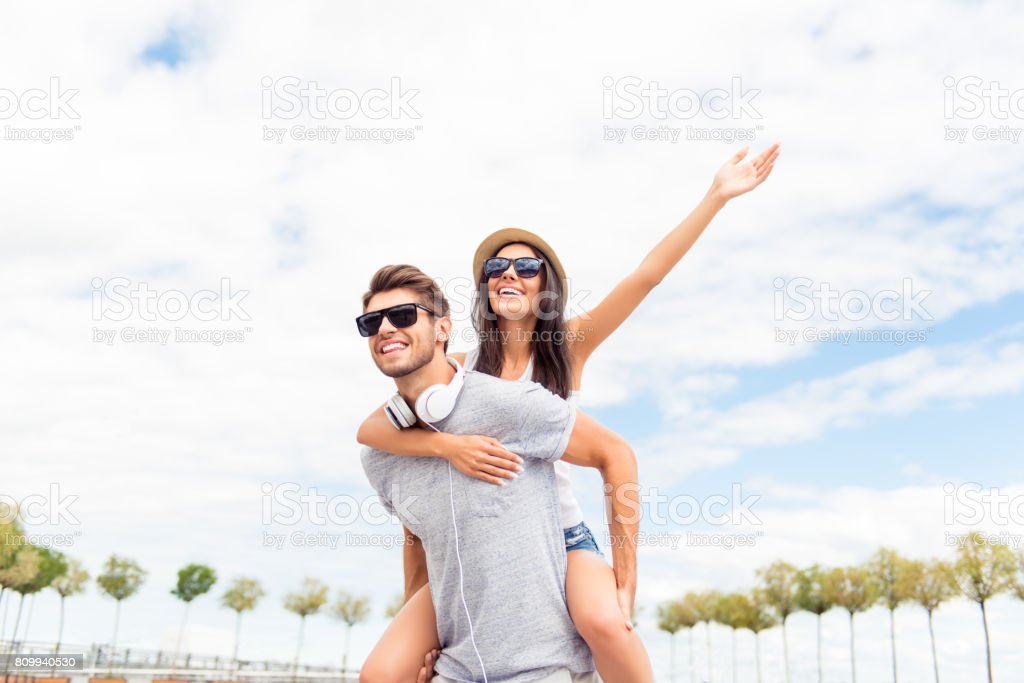 Young man piggybacking his happy girlfriend with raised hand. Cheerful lovers dreaming stock photo