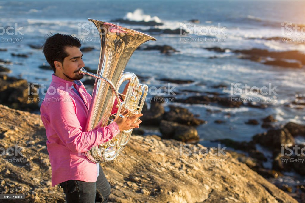 Young man play the trumpet on rocky sea coast during surf. stock photo