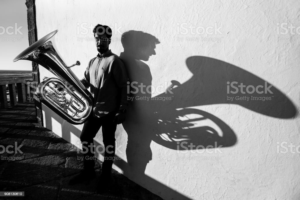 Young man play Tuba near the white wall the shadow of the tool. Black and white photo. stock photo
