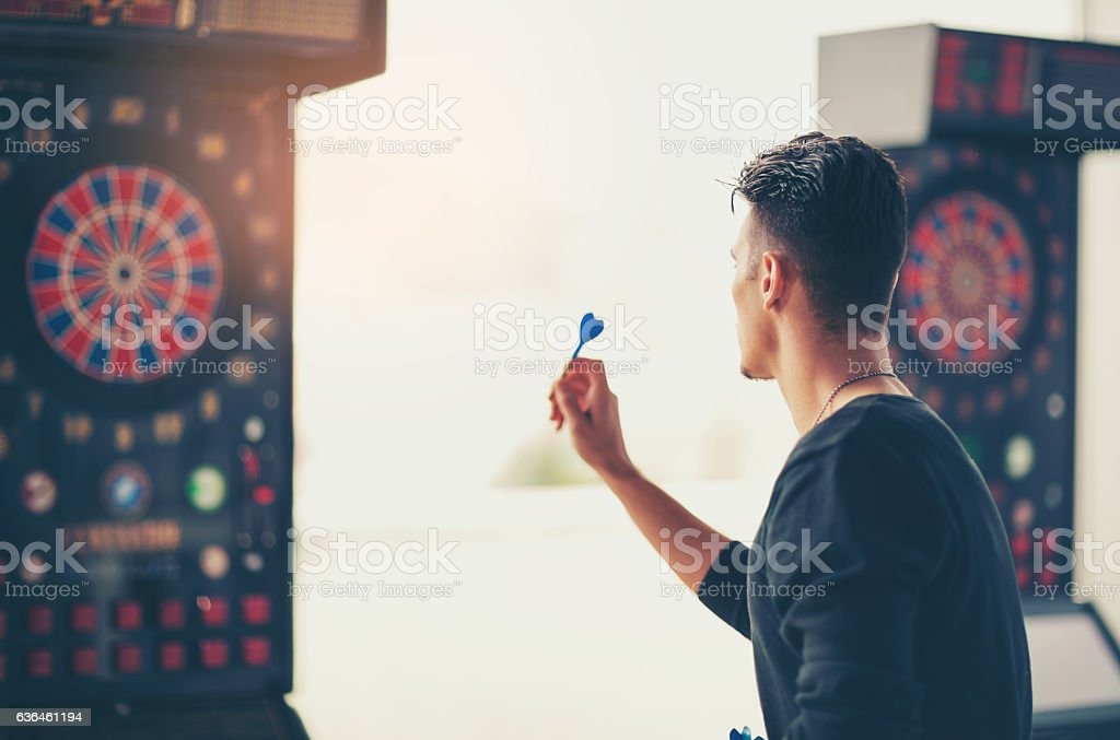 Young man playing a game shooting darts stock photo