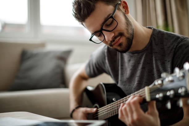 若い男が自宅のギター - ギター ストックフォトと画像