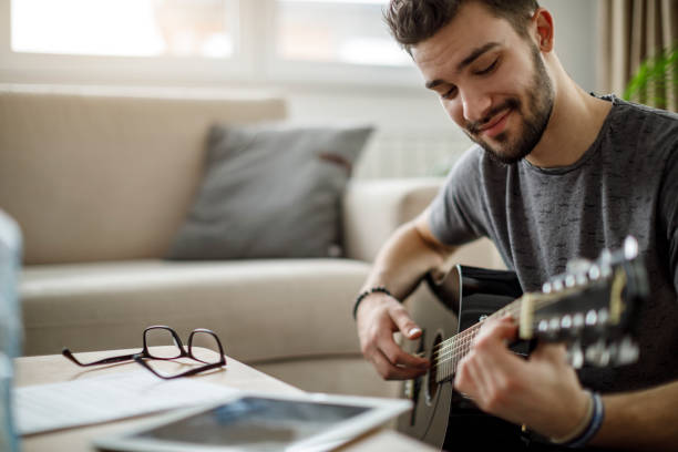 Young man playing a guitar at home stock photo