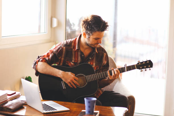 Young man playing a guitar Young man playing an acoustic guitar in a brightly lit room. On a desk in front of him is a laptop, coffe mug, and some books. His gaze is directed to his hands, while he tries to play a song. hobbies stock pictures, royalty-free photos & images