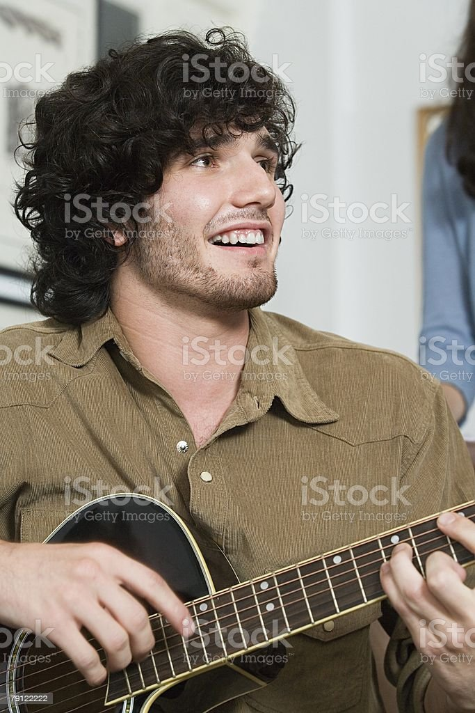 Young man playing a guitar royalty-free stock photo