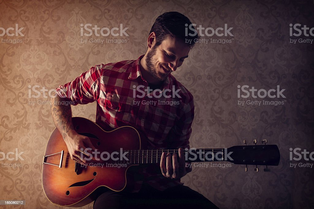 Young Man Playing a Vintage Guitar royalty-free stock photo