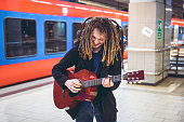 Young man playing acoustic guitar at the train station while waiting for his train