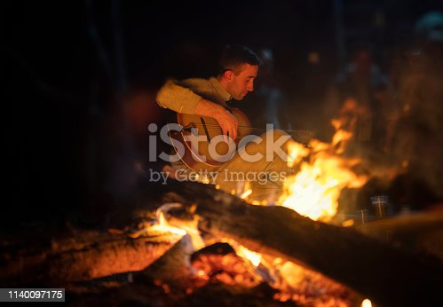 Young man playing acoustic guitar by the fire