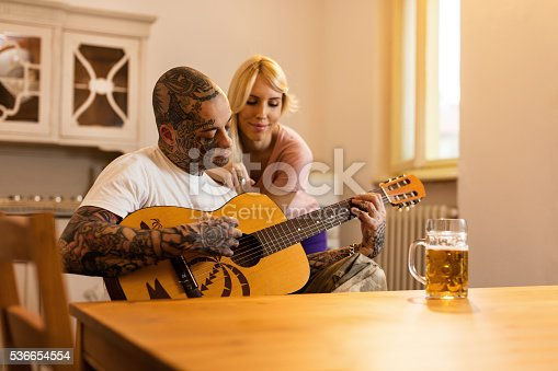 Tattooed man playing acoustic guitar while his smiling girlfriend in listening and enjoying the music.