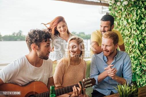 People looking at the musician with acoustic guitar at the party