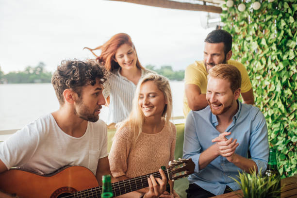 Young man playing acoustics guitar for his friends stock photo