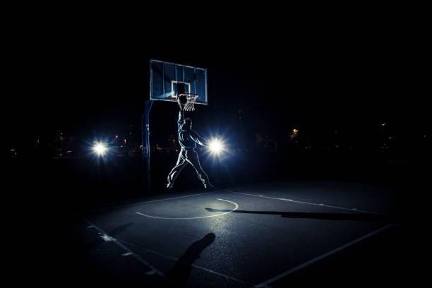Young man playing basketball at night stock photo