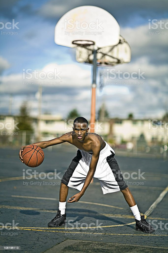 Young Man Playing Basketball on Court Outside royalty-free stock photo