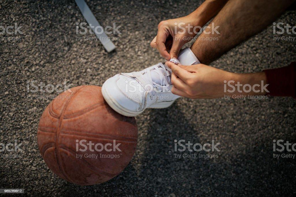 Young man playing basketball on his favorite court zbiór zdjęć royalty-free
