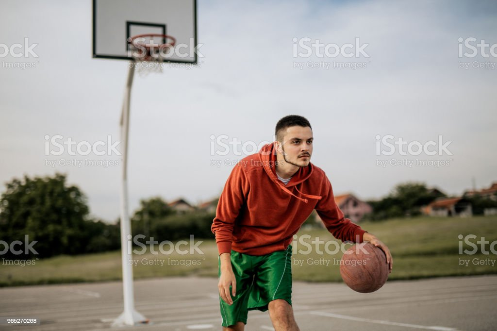 Young man playing basketball on his favorite court zbiór zdjęć royalty-free
