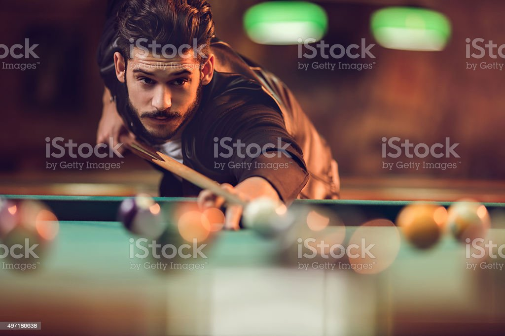 Young man playing billiard in a pool hall. stock photo