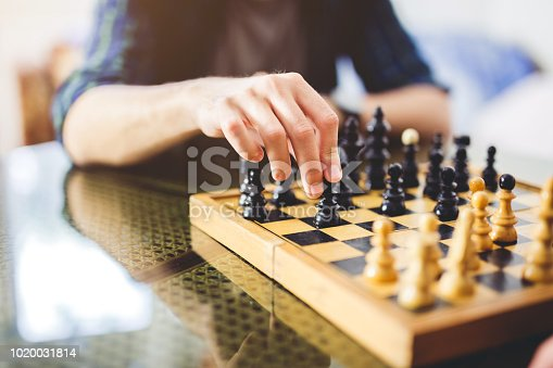 A closeup shot of a hand moving a black pawn piece across the chess board