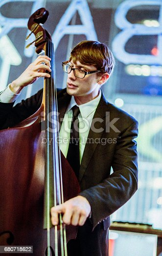 Young old-fashioned looking man wearing eyeglasses playing bass