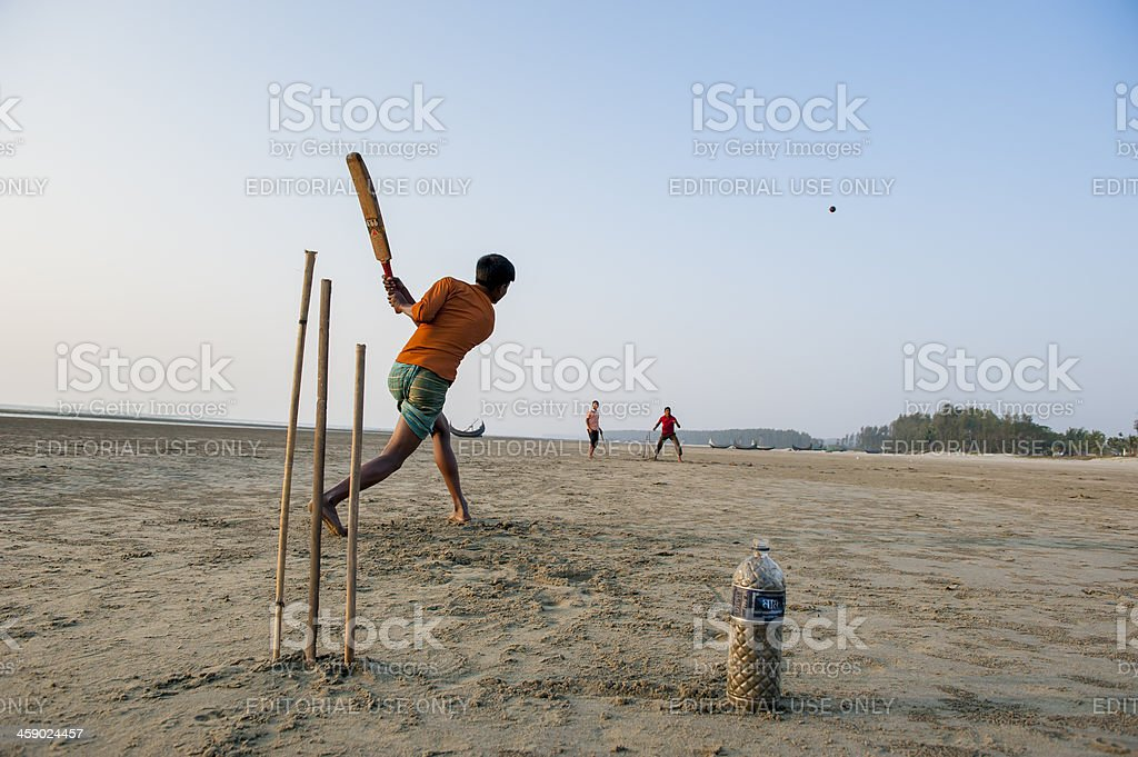 Young man playing cricket on the beach, Bangladesh stock photo