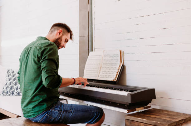 Young man playing electric piano at home studio Young man playing electric piano at home studio pianist stock pictures, royalty-free photos & images