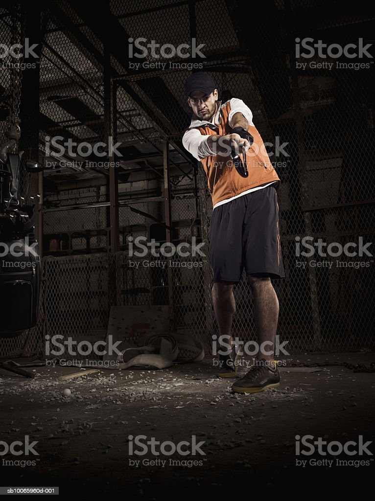 Young man playing golf in abandoned factory royalty-free stock photo