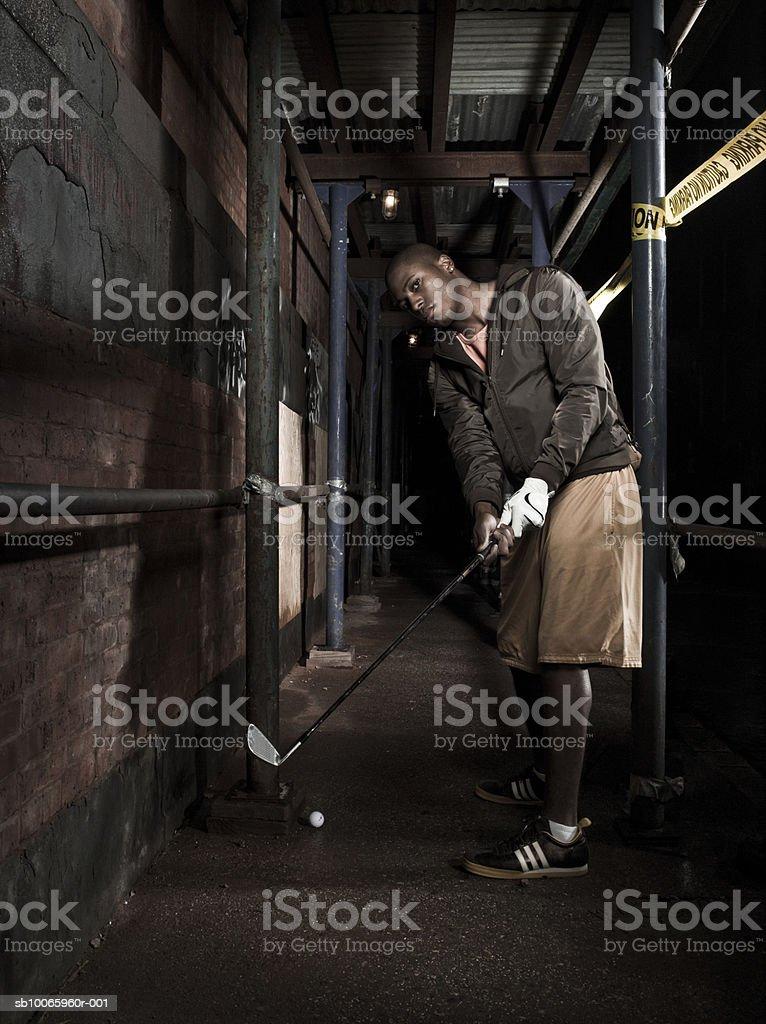 Joven jugando al golf en abandonado fábrica foto de stock libre de derechos