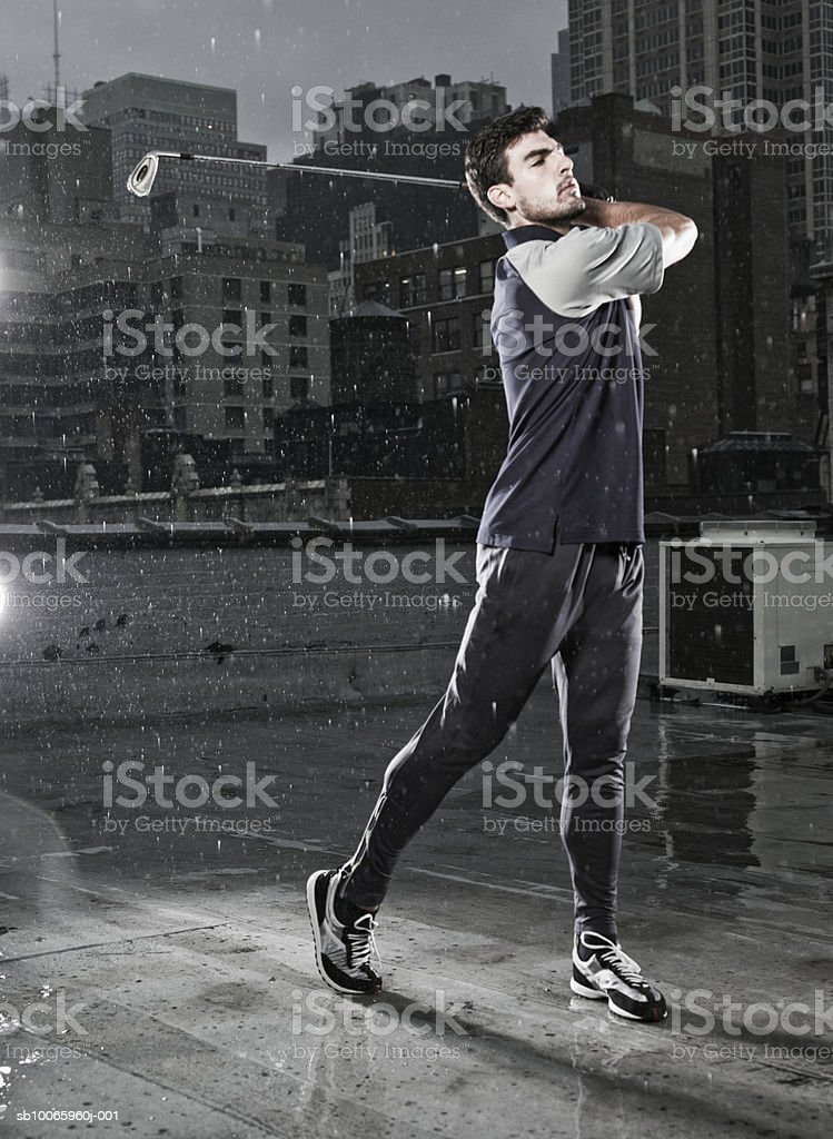 Young man playing golf in street royalty-free stock photo