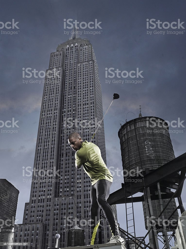 Young man playing golf in street, skyscraper in background, low angle view royalty-free stock photo
