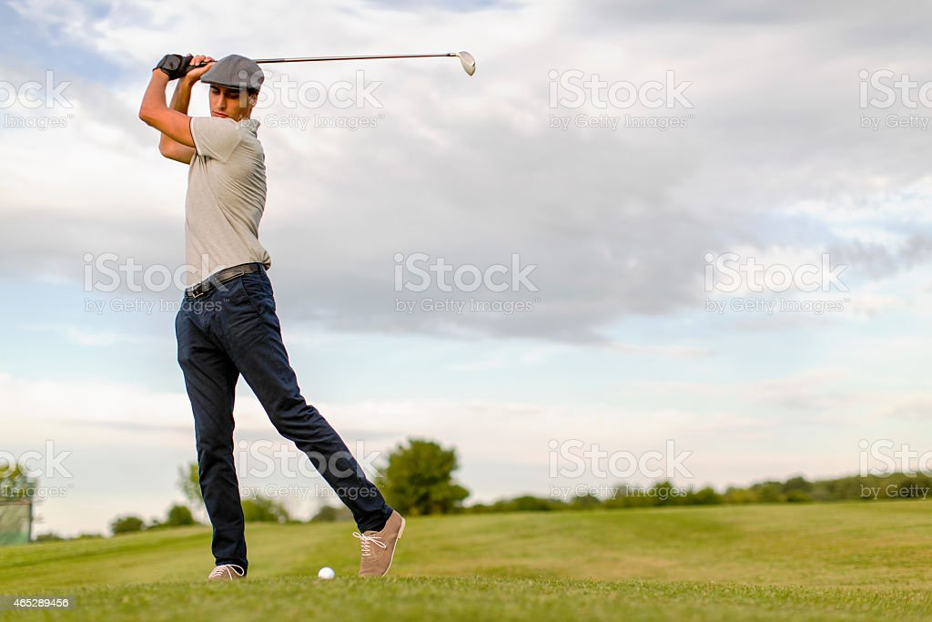 Young man playing golf stock photo