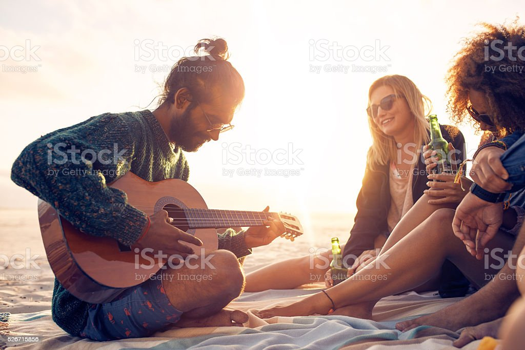Young man playing guitar for friends on the beach stock photo