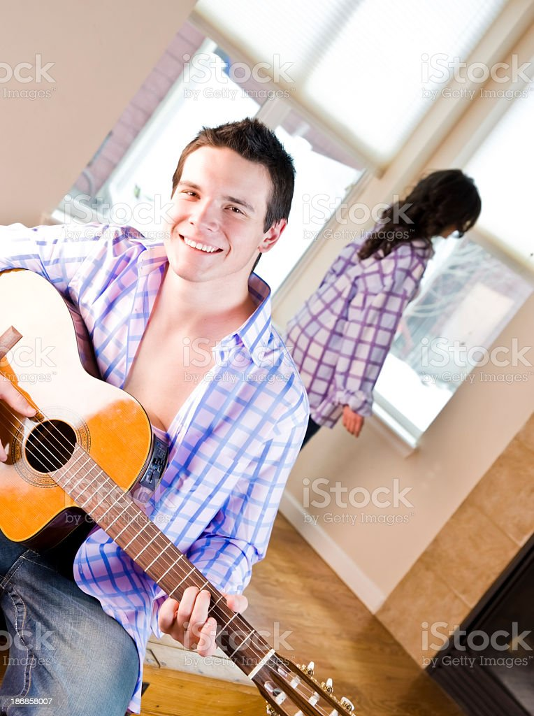 Young man playing guitar for girlfriend behind him stock photo