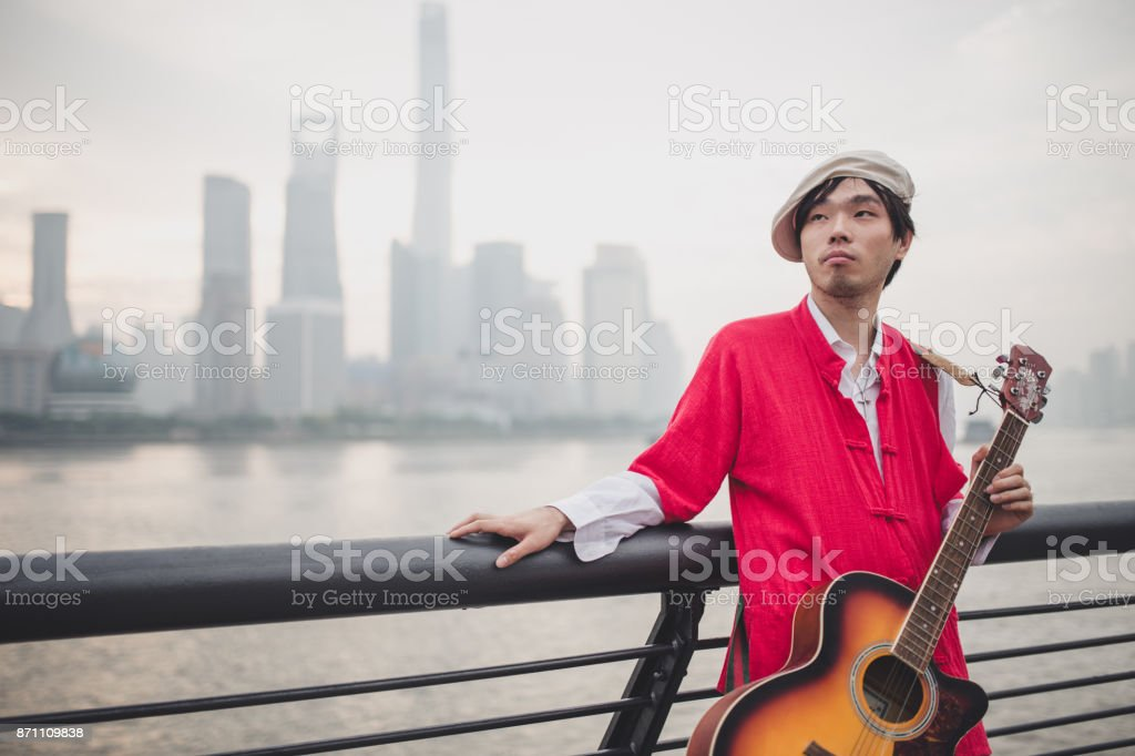 Young man playing guitar near the river stock photo