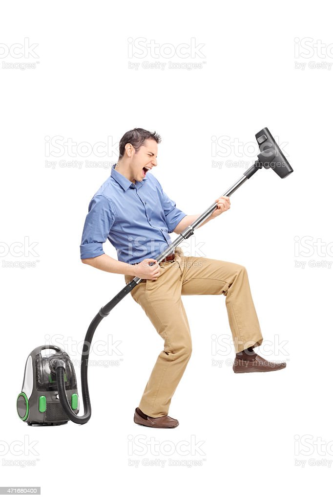 Young man playing guitar on a vacuum cleaner stock photo