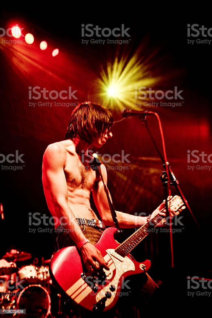 Young Man Playing Guitar on Stage at Concert royalty-free stock photo
