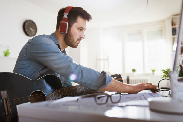 Young man playing guitar online stock photo