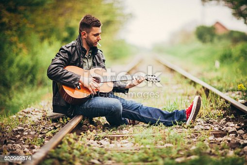 Young man playing acoustic guitar outdoors. He is sitting on a rusty vintage railroad tracks. Copy space available.