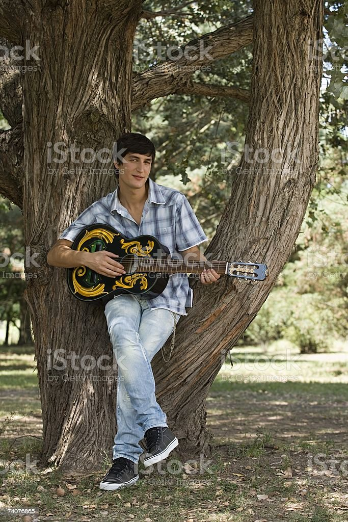 Young man playing guitar stock photo