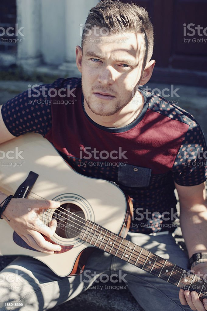 Young man playing his guitar royalty-free stock photo
