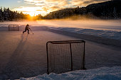 One adult skating on frozen lake during sunset, playing pond hockey.